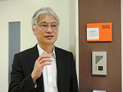 施設内の「東京営業所」の前で、「この技術で世界に貢献したい」と語る松浦社長